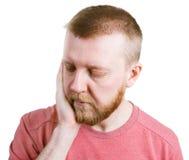 Бородатые владения человека дальше к его щеке стоковое фото rf