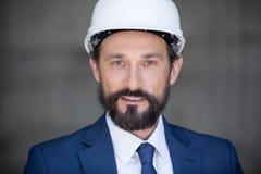 Бородатый бизнесмен в трудной шляпе усмехаясь на камере Стоковые Фото