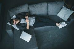 Бородатый молодой человек в eyeglasses и наушниках используя smartphone пока лежащ на софе Стоковая Фотография