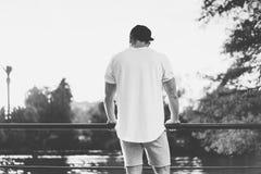 Бородатый мышечный человек нося пустые футболку, крышку snapback и шорты в временени Ослаблять около озера Позеленейте город Стоковая Фотография