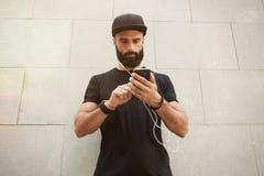Бородатый мышечный человек нося черное временя крышки Snapback пробела футболки Молодые человеки стоя напротив пустого серого бет Стоковое фото RF