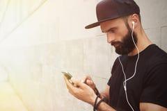 Бородатый мышечный человек нося черное временя крышки Snapback пробела футболки Молодые человеки стоя напротив пустого серого бет Стоковые Фото