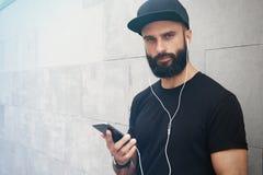 Бородатый мышечный человек нося черное временя крышки Snapback пробела футболки Молодые человеки усмехаясь напротив пустого серог Стоковая Фотография RF