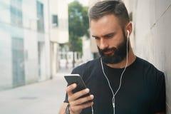 Бородатый мышечный человек нося черное временя крышки Snapback пробела футболки Молодые человеки используя смотреть наушников Sma Стоковые Фотографии RF