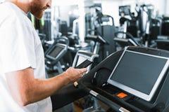 Бородатый парень в спортзале на третбане Стоковая Фотография RF