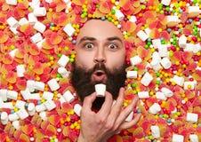 Бородатый парень окруженный с сладостным веществом Стоковое фото RF