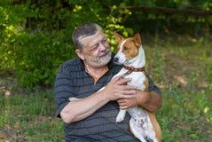 Бородатый старший человек принимая его милому dogin руки Стоковое фото RF