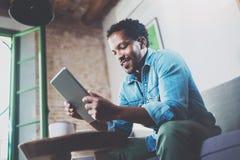 Бородатый усмехаясь африканский человек используя таблетку для видео- переговора пока ослабляющ на софе в современном офисе Конце Стоковое Фото