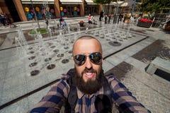 Бородатый фотограф делает selfie на предпосылке города, собственную личность po Стоковое Изображение