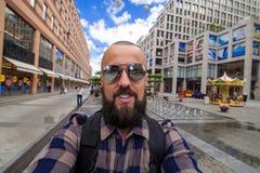 Бородатый фотограф делает selfie на предпосылке города, собственную личность po Стоковое Изображение RF