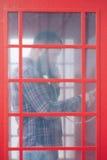 Бородатый человек вызывая от телефонной будки Стоковые Фото