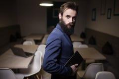 Бородатый человек в костюме и с таблеткой в кафе; Стоковое Изображение RF