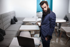 Бородатый человек в костюме с компьтер-книжкой и чашкой кофе в кафе; Стоковые Фотографии RF