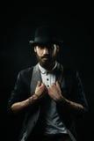 Бородатый человек в котелке держа его отвороты Стоковые Фото