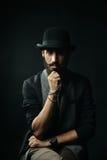 Бородатый человек в котелке касаясь его бороде Стоковое Изображение