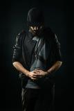 Бородатый человек в куртке стоит с его обхватыванной головой и holdi Стоковое Изображение