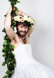 Бородатый человек в платье свадьбы женщины на ее нагом теле, льнуть к лозе На его голове венок цветков смешно стоковые изображения