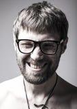 Бородатый человек в стеклах играет дурачка шальной человек, смешное выражение Стоковое Фото