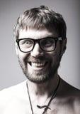 Бородатый человек в стеклах играет дурачка шальной человек, смешное выражение Стоковые Фото