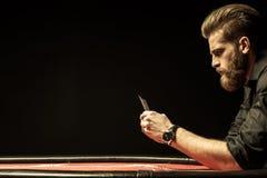 Бородатый человек держа карточки покера на черноте стоковая фотография rf