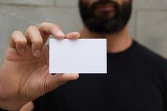 Бородатый человек нося вскользь черную футболку показывая пустую белую визитную карточку Запачканное частное предпосылки готовое  Стоковое Изображение RF