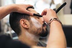 Бородатый человек получая стрижку бороды с бритвой парикмахером стоковая фотография rf