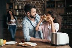 Бородатый человек смотря милые здравицы удерживания маленькой девочки в кухне Стоковая Фотография