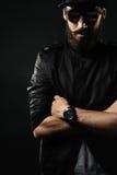 Бородатый человек с приспособленной шляпой сложил его оружия через его комод Стоковые Фотографии RF