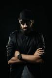 Бородатый человек с солнечными очками сложил его оружия через его комод Стоковое фото RF