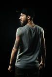 Бородатый человек с татуировками стоит назад Стоковые Фотографии RF