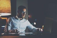 Бородатый элегантный сотрудник в eyeglasses работая на офисе на ноче использование человека компьтер-книжки Горизонтальный, влиян Стоковые Изображения