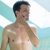 Борода отделки молодого человека перед зеркалом Стоковые Изображения