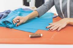 Бортовое veiw ` s женщины вручает рисовать картину на яркой голубой ответной части Стоковое фото RF