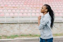 Бортовой портрет атлетической афро-американской девушки jogging вдоль стадиона пока слушающ к музыке в наушниках Стоковые Изображения