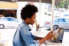 Бортовой портрет женщины используя мобильный телефон с компьтер-книжкой Стоковая Фотография RF
