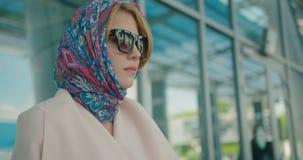 Бортовой портрет конца-вверх молодой привлекательной белокурой женщины в бежевом пальто, красочном шарфе на ее голове и солнечных акции видеоматериалы
