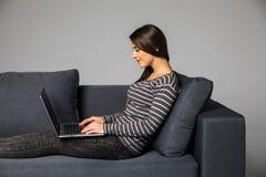 Бортовой портрет красивой молодой женщины сидя на софе и используя компьтер-книжку в доме Стоковые Изображения RF
