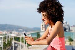 Бортовой портрет молодой женщины с мобильным телефоном наушников внешним держа Стоковое Фото
