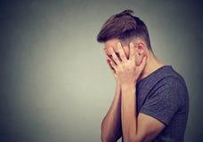 Бортовой профиль унылого молодого человека с руками на стороне смотря вниз Разлад депрессии и тревожности стоковые фото