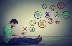 Бортовой человек профиля работая на компьтер-книжке используя социальное применение средств массовой информации сидя на поле стоковое изображение rf