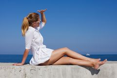 Босоногая девушка в белом коротком платье сидит полагаться в наличии и смотреть прочь с забралом руки стоковое фото