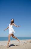 Босоногая девушка в белом платье прыгает на seashore песка Стоковая Фотография