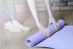 Босоногая женщина переплетает фиолетовые циновку и фитнес йоги на поле партера Стоковое фото RF