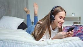 Босоногая молодая милая девушка лежа на кровати в музыке спальни слушая используя наушники и смартфон видеоматериал