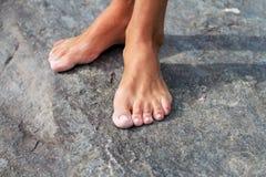 Босоногая нога ` s женщины на горячем утесе стоковое изображение