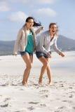 2 босоногих подруги смеясь над на пляже Стоковые Фотографии RF