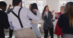Босс возбужденного молодого счастливого брюнета женский в официальных одеждах празднуя успех танцуя с жизнерадостными разнообразн акции видеоматериалы