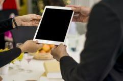 Босс держит таблетку в взгляде секретарши руки, на партии в офисе, с изолированным экраном, впечатляющая концепция цифрового дела стоковое изображение