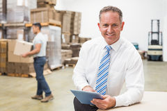 Босс используя цифровую таблетку в складе Стоковое Фото
