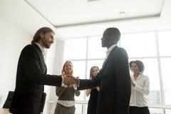 Босс и команда оценивая черного бизнесмена рукопожатием и ap Стоковая Фотография
